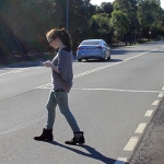 Teenager texting while walking across a road